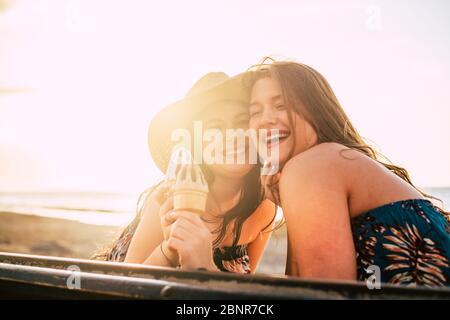 Joyeuse et le bonheur concept avec des gens joyeux couple heureux de jeunes filles caucasiennes avec la glace et l'été fond ensoleillé à la plage pendant les vacances Banque D'Images