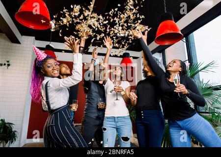 Confetti volant autour d'un groupe africain célébrant une fête avec l boissons dans leurs mains Banque D'Images