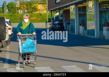 Vieille femme italienne, pensionnée portant un masque facial coronavirus poussant son panier à l'extérieur d'une épicerie. Lady craint pour la pandémie de COVID-19.