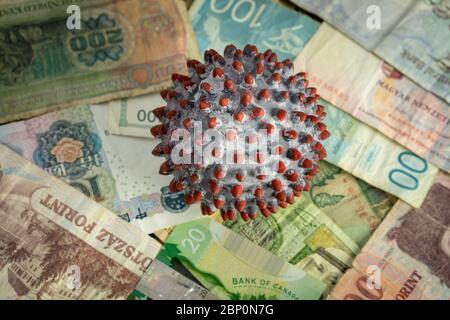 Une balle peinte comme un virion du COV-2 du SRAS au milieu de nombreux billets de différents pays Banque D'Images