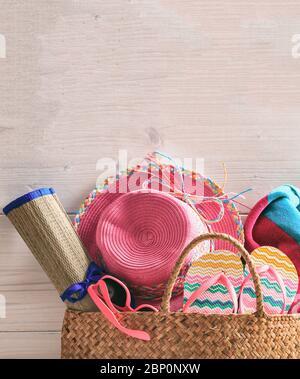 Sac de plage d'été et accessoires sur fond de bois rose. Chapeau de paille, tongs, lunettes de soleil et serviette. Photo verticale, espace de copie. Banque D'Images