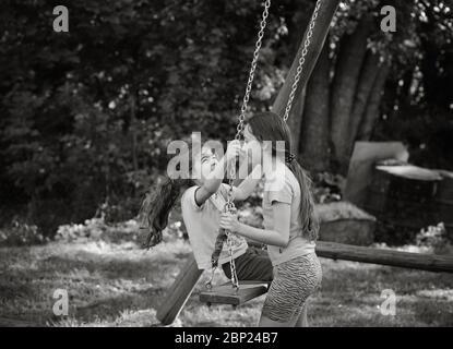 Deux belles filles heureuses jouant sur l'oscillation et souriant à la chaude journée d'été