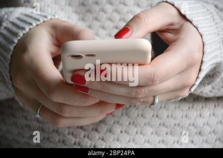 Gros plan femme avec ongles rouges à l'aide de son téléphone portable. Envoi d'un message avec un smartphone. Vue avant
