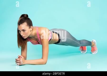Planche parfaite. Pleine longueur de jeune belle femme dans les vêtements de sport faisant le plank sur fond bleu. Prise de vue en studio. Sport et fitness Banque D'Images