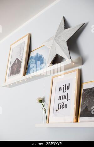 Étagères murales décorées avec une composition de gravures, une étoile en bois et des guirlandes lumineuses. Banque D'Images
