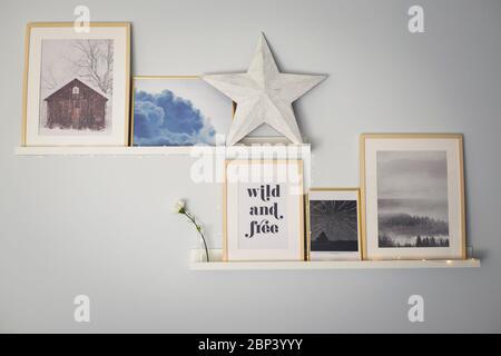 Étagères murales décorées avec une composition de gravures, une étoile en bois et des guirlandes lumineuses. Décoration maison. Banque D'Images