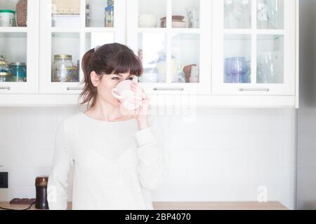 Jolie femme caucasienne, avec des lanières et de la queue de cheval, buvant une tasse de café le matin dans une cuisine blanche et lumineuse. Banque D'Images