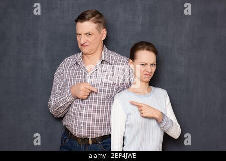 Studio demi-portrait de couple caucasien en colère et agacé, pointant avec les index les uns contre les autres comme faire des accusations mutuelles, sur gra Banque D'Images