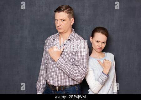 Studio portrait en demi-longueur d'homme et de femme caucasiens en colère et mécontents, vêtus de vêtements décontractés, pointant les pouces les uns contre les autres, sur gris Banque D'Images