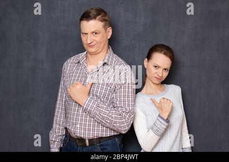 Studio taille-vers le haut portrait de l'homme et la femme caucasiens, pointant avec les pouces l'un contre l'autre, étant en colère et agacés, ayant des revendications mutuelles, sur bac gris Banque D'Images