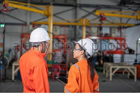 Mécanicien et femme ingénieur parlant à l'usine Banque D'Images