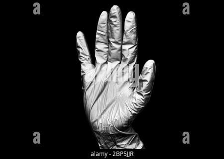 Main humaine dans un gant médical en caoutchouc blanc sur fond noir isolé de près, une main chirurgien dans un gant de protection en latex, main médecin dans un gant