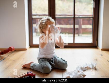 Petit garçon malade avec froid à la maison assis sur le sol, éternuant. Banque D'Images