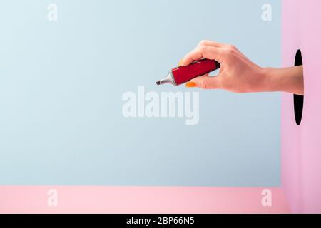 Main tenant un marqueur rouge à pointe feutre sur fond bleu et rose Banque D'Images