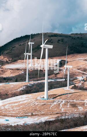 Moulin à turbine électrique sur un terrain de ferme enneigé. Vue sur le paysage de la colline en hiver depuis le sommet. Banque D'Images