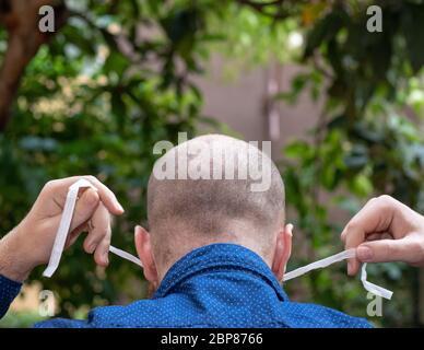 Vue arrière d'un homme chauve mettant un masque de visage et l'attacher derrière sa tête