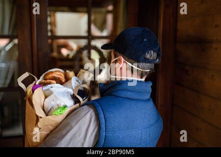 Vue arrière du coursier avec masque de visage livrant le shopping, virus corona et le concept de quarantaine. Banque D'Images