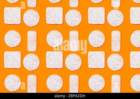 Motif composé de craquelins de riz ou de gâteaux de riz sur fond orange. Aliments biologiques sains. Pose à plat. Banque D'Images