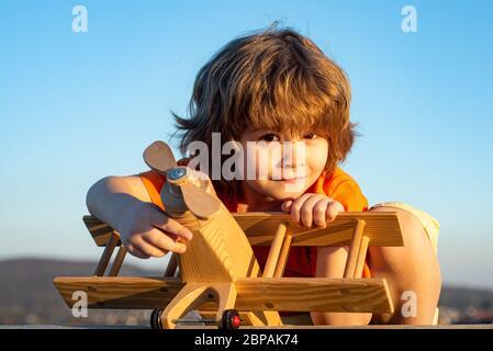Un enfant heureux rêve de voyager et de jouer avec un avion jouet. Petit pilote aviateur en extérieur sur fond bleu ciel d'été. Rêves d'enfant