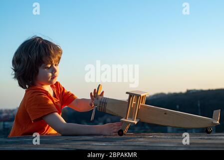Petit garçon avec avion en bois. Un enfant rêve de devenir pilote. Rêves d'enfant et imagination concept. Enfance à la campagne