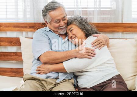 Couple asiatique grand-parent embrassant ou embrassant avec le sentiment heureux dans la maison, romantique et amoureux de la Valentin ou anniversaire, long live et El