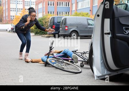 Jeune femme appelant ambulance après avoir frappé accidentellement un cycliste masculin avec sa voiture Banque D'Images