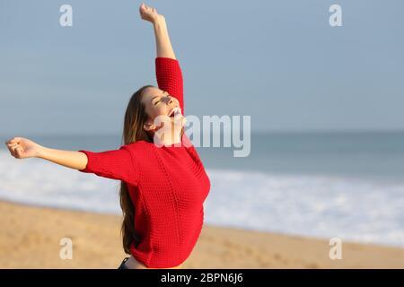 Girl in red excité la célébration des vacances sur une plage raising arms