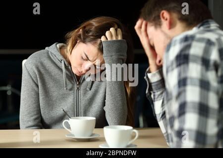 Un triste couple d'adolescents se plaignent de s'asseoir dans un bar la nuit Banque D'Images