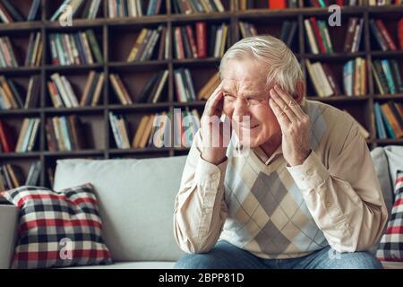 Homme âgé seul assis à la bibliothèque ayant un mal de tête terrible Banque D'Images