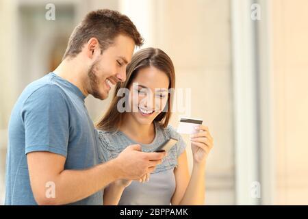 Un couple heureux payant en ligne avec une carte Crebest et un smartphone dans la rue Banque D'Images