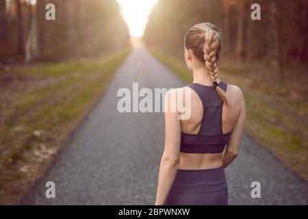 Jeune femme sportive en bonne santé marchant au lever du soleil le long d'une route rurale à travers une forêt dense vers la lueur du soleil à la fin entre les arbres dans un