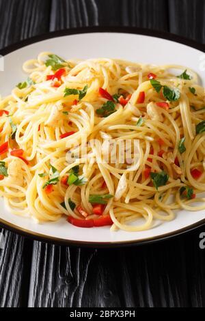 Naples traditionnelle Aglio e Olio spaghetti gros plan dans une assiette sur la table. Verticale Banque D'Images