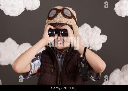 un garçon joue avec des jumelles et rêve de devenir pilote, habillé dans une veste rétro et un casque avec des lunettes, des nuages de laine de coton, un dos gris