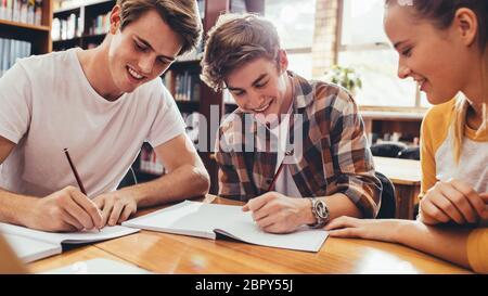 Groupe d'élèves assis à la table dans la bibliothèque et étudiant ensemble. De jeunes amis heureux travaillant sur le projet de lycée.