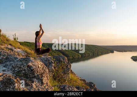 Jeune fille faisant yoga exercice de forme physique dans le lever du soleil matin à l'extérieur dans la prairie magnifique paysage de montagnes