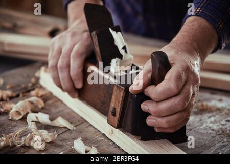 Mains d'un menuisier ébéniste, menuisier ou à l'aide d'un plan d'époque pour lisser la surface d'une planche de bois sur son workbench