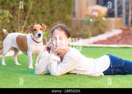 Portrait de la belle jeune adolescente avec son chien en utilisant le téléphone mobile à l'arrière-cour.Brunette petite fille parlant sur le téléphone mobile extérieur.chien attend impatiemment de jouer avec elle. Focus sélective fille.