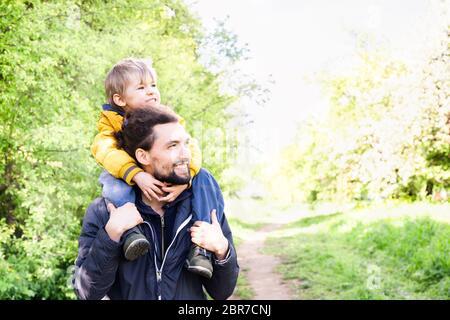 Une promenade en famille à l'extérieur. Père de son petit fils sur ses épaules dans un parc. Fête des pères et concept de détente en famille