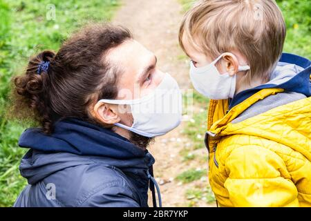 Protection familiale pendant une pandémie de coronavirus. Gros plan père et petit fils dans des masques protecteurs au front regardant l'un l'autre à l'extérieur Banque D'Images