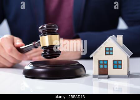 Close-up d'une main du juge Gavel frappant près de la maison modèle sur le tableau blanc Banque D'Images