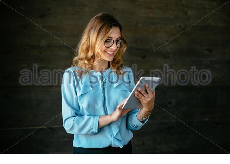 Charmant jeune businesswoman using a tablet, dactylographie, chercher quelque chose. Vêtu d'un élégant chemisier, dans les lunettes. Banque D'Images