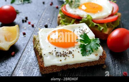 Toasts de seigle avec purée d'avocat, œuf frit, tomate fraîche, herbes. Petit déjeuner savoureux. Une alimentation adéquate. Sandwich avec œuf. Banque D'Images