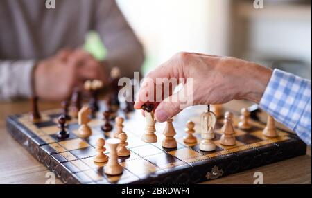 Mi-section d'amis hommes âgés à la maison, jouant aux échecs.