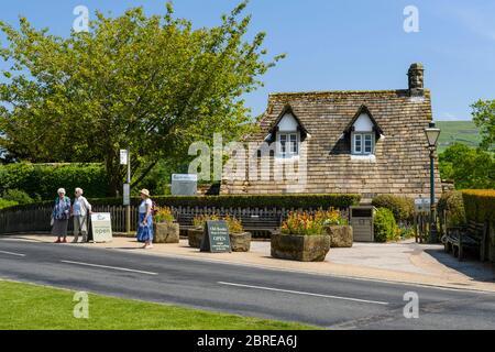Extérieur de pittoresque chalet salon de thé café dans village rural pittoresque (3 femmes attendent par arrêt de bus) - Bolton Abbey, Yorkshire Dales, Angleterre Royaume-Uni
