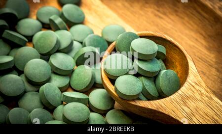 Algues vertes en comprimés - chlorelle, spiruline en cuillère en bois sur fond de bois - gros plan