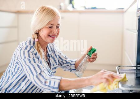 Portrait d'une femme âgée qui nettoie un four dans la cuisine à l'intérieur à la maison.