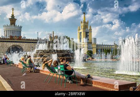 MOSCOU - 29 JUILLET 2016 : les touristes se reposent près de la fontaine de fleurs de pierre dans le parc des expositions de toute la Russie (VDNKh). Cette fontaine a été construite en 1954.