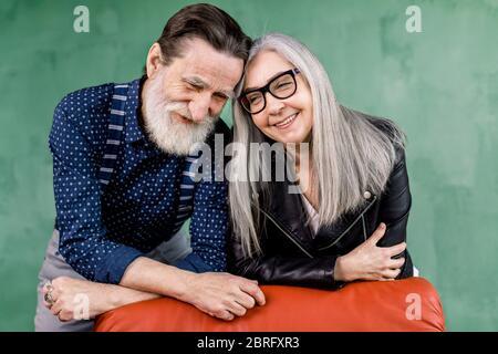 Un beau couple de personnes âgées souriant, amoureux de passer du temps ensemble, assis sur une chaise rouge et en touchant les fronts, tout en restant debout dans une pièce moderne en face de Banque D'Images