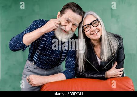 Couple âgé. Joyeux couple âgé souriant tout en étant dans une bonne humeur, se pencher sur la chaise douce rouge et toucher les fronts. Portrait romantique