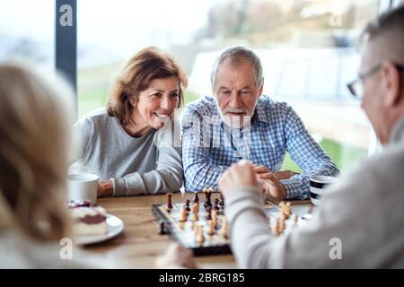 Groupe d'amis senior à la maison, jouant à des jeux de société.